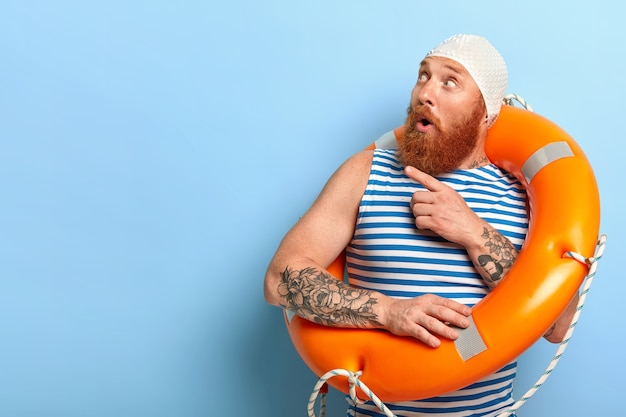 Surprised unshaven male vacationist dressed in bathingcap and striped vest