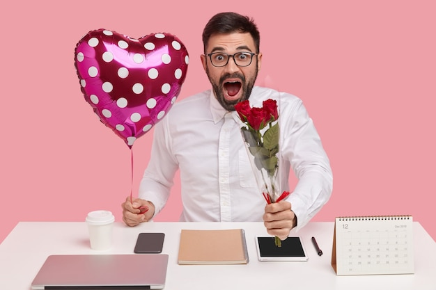 Il giovane maschio con la barba lunga sorpreso porta bouquet e palloncino a forma di san valentino, scioccato nel sentire un complimento