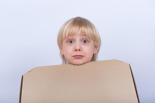 Удивленный расстроенный белокурый мальчик с коробкой в руке на белой предпосылке. доставка пиццы