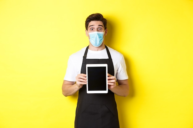 노란색 벽 위에 서있는 검은 앞치마와 태블릿 화면을 보여주는 의료 마스크에 놀란 웨이터
