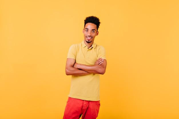 팔으로 포즈를 취하는 놀란 잘 차려 입은 아프리카 모델이 교차했습니다. 자신감이 포즈에 서 놀된 남자의 실내 샷.