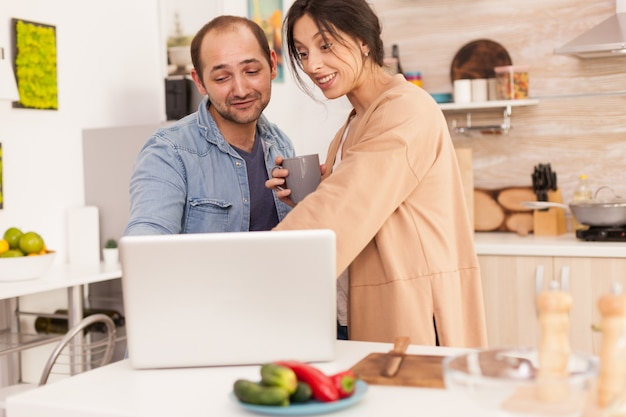 Surprised wife looking at laptop in kitchen with cup of coffee in hand. happy entrepreneur husband. happy loving cheerful romantic in love couple at home using modern wifi wireless internet technology