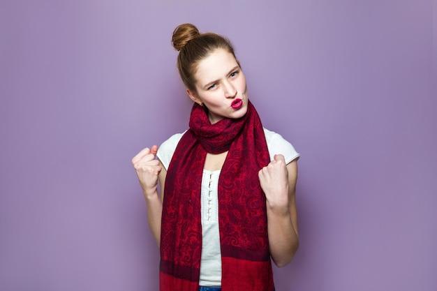 びっくりした勝者の女性。集められた髪、そばかす、赤いスカーフが紫色の背景、感情、表現、成功のコンセプトに興奮し、勝利を祝う若い感情的な美しさ。