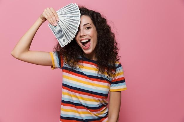 ピンクで隔離されたドルのお金のファンを保持している巻き毛の20代の女性を驚かせた