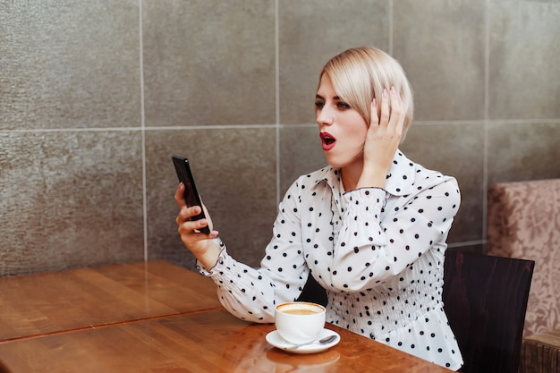 Surprised woman in cafe looking at smartphone