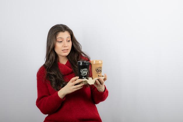 驚いた女性のコーヒーの紙コップ。