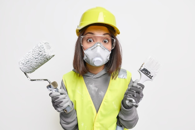 驚いた女性の建設マネージャーは、建築ツールを保持し、作業服を着て修理するあなたの家の品質を保証します