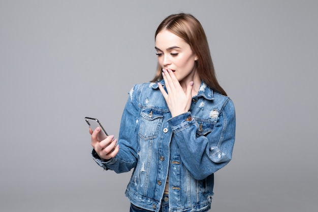 Surprised woman covering mouth, looking at mobile phone screen, shocked female reading unexpected message, shopping offer, good news, holding cellphone, isolated on grey wall
