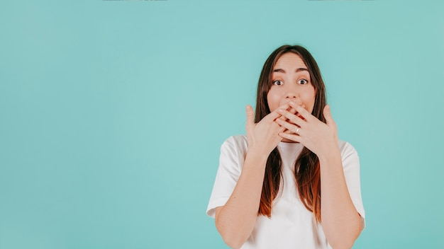 Surprised woman covering mouth with hands