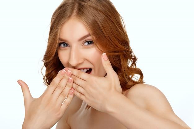 手のひらで口を覆っている驚きの女性。ショックと驚きのポーズで大きく開いた口を閉じます。人間の顔の表情と感情。