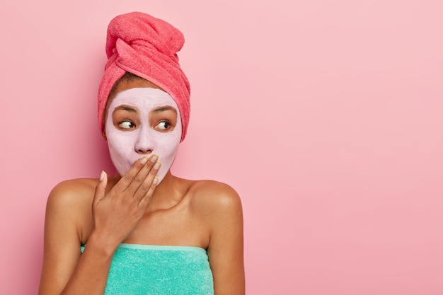 Surprised woman covers mouth, applies nourishing mask for removing dead cells, wears wrapped towel on head, stands against pink wall