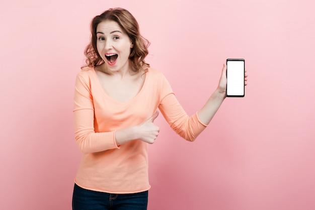 Удивленная женщина демонстрирует в руке экран телефона.