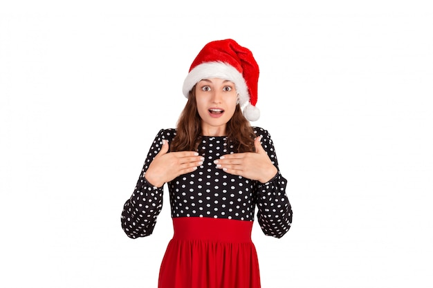 Surprised woman in dress holding hands on breast smiling being touched and pleased. emotional girl in santa claus christmas hat isolated