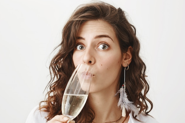 Surprised woman drinking champagne at gossiping