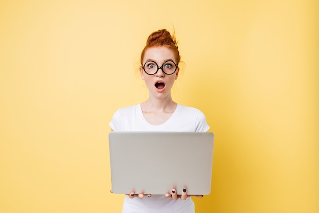 Surprised woman in eyeglasses holding laptop computer