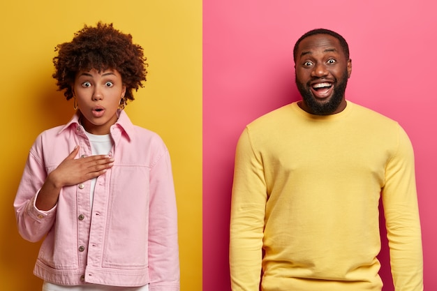 Surprised woman gasps from wonder, keeps hand on chest, happy dark skinned guy stands near, giggles positively over funny joke. afro american couple express different emotions shock and positiveness
