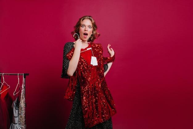 Удивленная женщина собирается примерить сверкающее красное платье