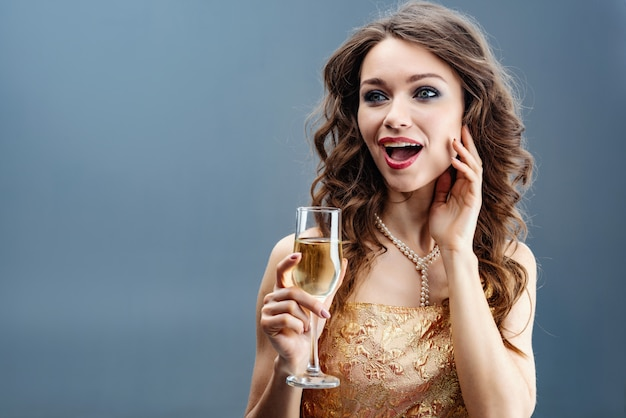 Surprised woman in golden dress and pearl necklace with raised glass of champagne and touch herself face for hand