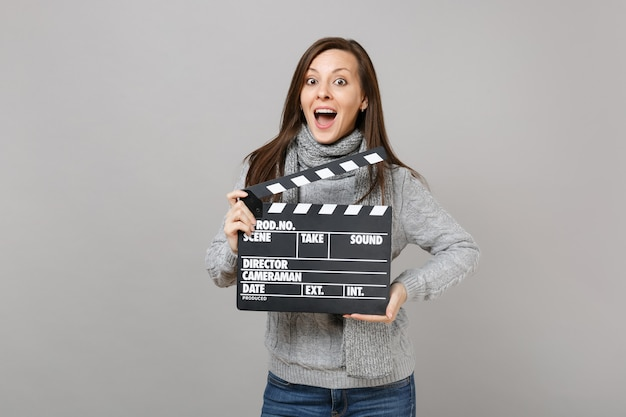 Surprised woman in gray sweater, scarf keeping mouth wide open hold classic black film making clapperboard isolated on grey background. healthy fashion lifestyle, people emotions, cold season concept.