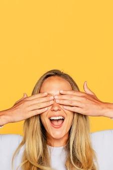彼女の目を覆っている驚いた女性の手