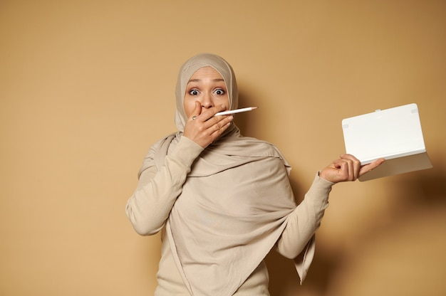 Surprised woman in hijab holds a note pad and pencil in her hands and cover her mouth expressing confusion