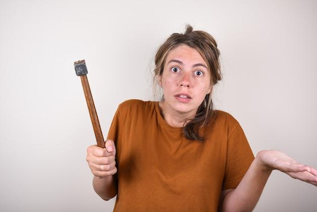 Удивленная женщина, держащая в руках молоток, не умеющая делать ремонт в доме. женщина с молотком удивлена вопросом. концепция выбора строительных материалов