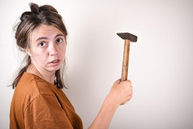 Удивленная женщина с молотком в руках, которая не умеет делать ремонт в доме