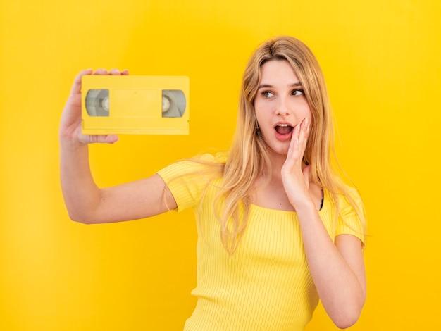 Удивленная женщина, держащая кассету