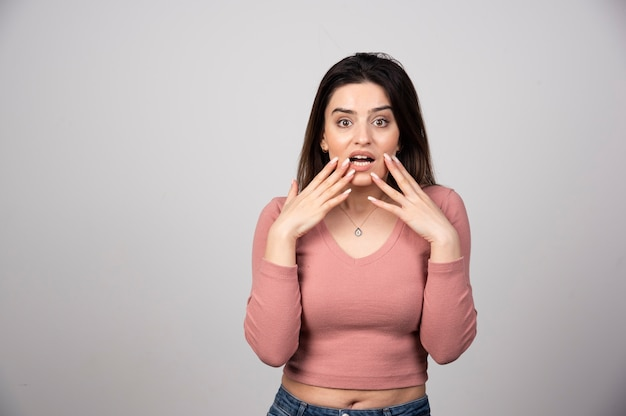 Surprised woman holding cheeks by hands on a gray wall.