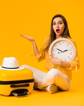 Surprised woman holding clock next to luggage with hat on top