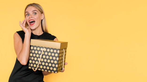 Surprised woman holding gift box copy space