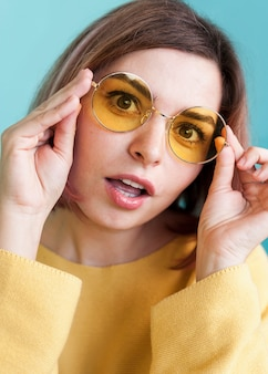 Surprised woman holding glasses close up