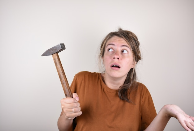 Surprised woman holding a hammer in her hands