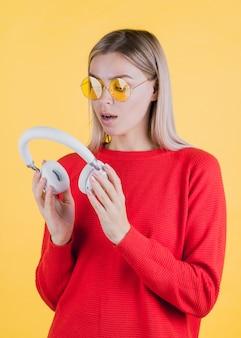 Surprised woman holding headphones medium shot