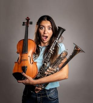 Удивленная женщина, держащая музыкальные инструменты на сером