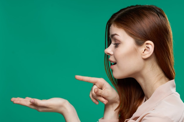 Surprised woman holding palms in front of her emotions side view close-up green.
