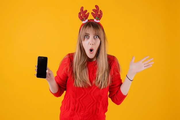 Surprised woman holding phone with blank screen wearing funny christmas hoop