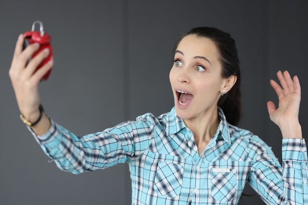 Surprised woman holding red alarm clock in her hands. time management concept