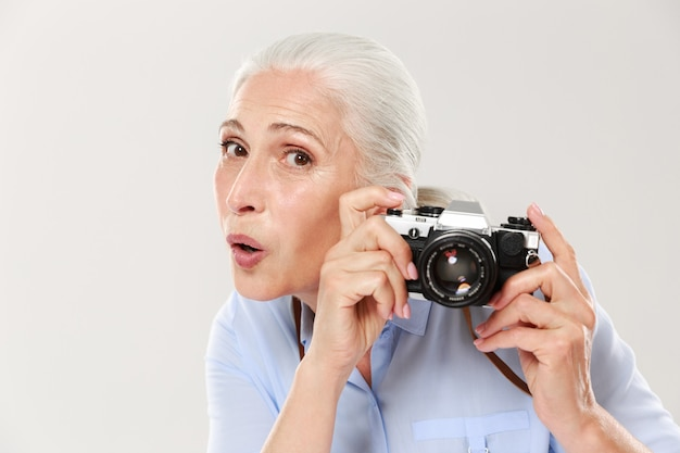 Surprised woman holding retro camera