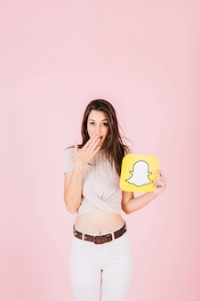 Surprised woman holding snapchat icon on pink background