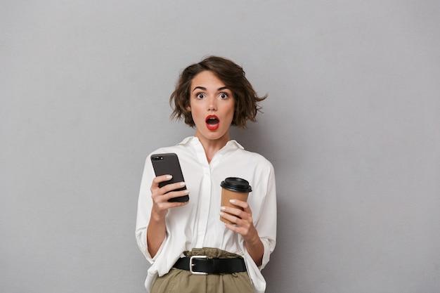 テイクアウトコーヒーを保持し、携帯電話を使用して、灰色の壁に隔離された女性