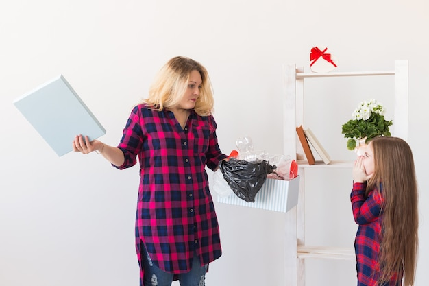 Surprised woman holds box with plastic trash