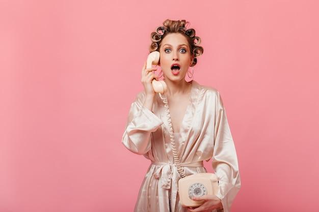 Удивленная женщина в халате смотрит вперед и держит стационарный телефон на изолированной стене