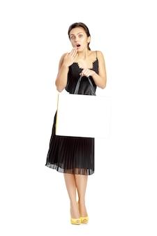 흰색 배경에 고립 된 쇼핑 가방과 함께 검은 드레스에 놀란 된 여자.