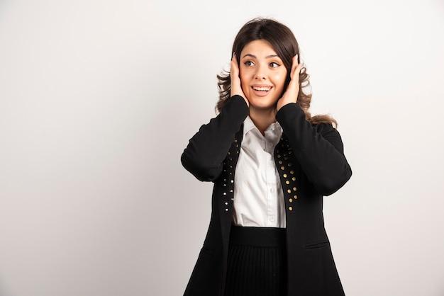 黒のジャケットを着た驚いた女性が耳を覆った。