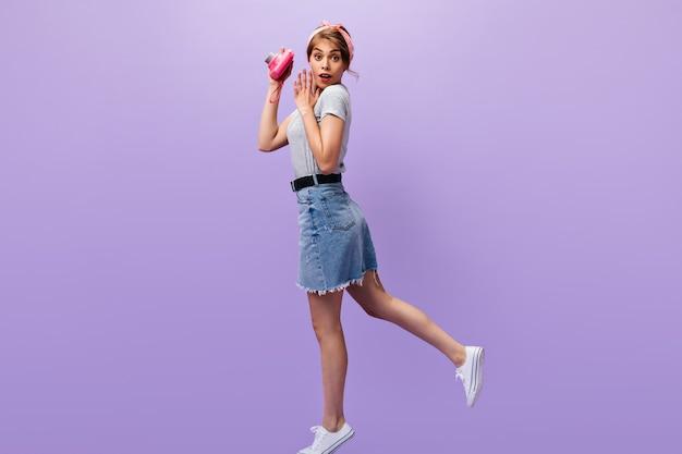 デニムスカートのびっくりした女性がピンクのカメラを持っています。灰色のシャツと白いスニーカーのポーズで夏のヘッドバンドを持つ素敵な女の子。