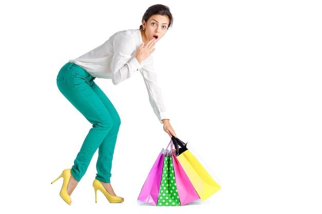 흰색 배경에 고립 된 쇼핑 가방 녹색 바지에 놀란 된 여자