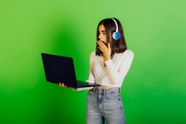 ノートパソコンを持って、興奮して手を上げているヘッドフォンで驚いた女性は、オンラインで衝撃的なニュースを受け取りました。