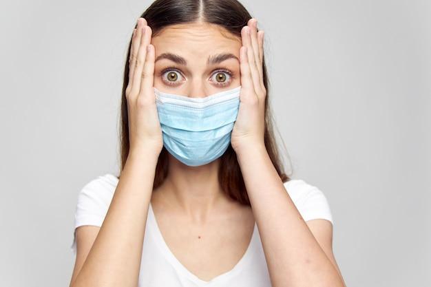 Удивленная женщина в медицинской маске трогает лицо руками