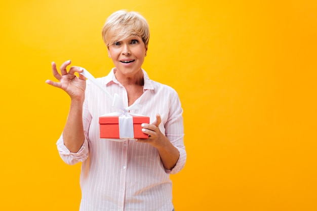 Удивленная женщина в розовой рубашке держит подарочную коробку